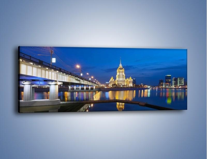 Obraz na płótnie – Oświetlony budynek mieniący się w tafli wody – jednoczęściowy panoramiczny AM119