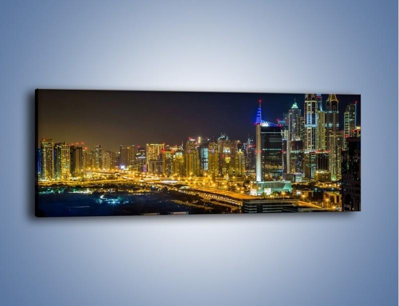 Obraz na płótnie – Oświetlony Dubaj nocą – jednoczęściowy panoramiczny AM506