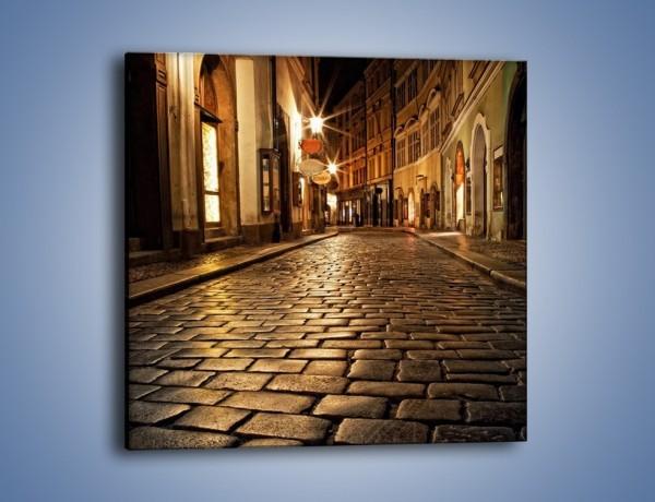 Obraz na płótnie – Wybrukowana uliczka w świetle nocnych lamp – jednoczęściowy kwadratowy AM060